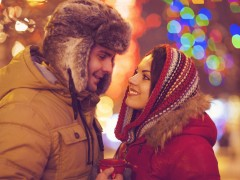 Happy couple in love outdoor in evening Christmas lights