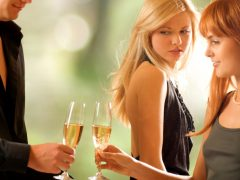 Young couple toasting with champagne and woman looking at them with jealousy, focus on blonde
