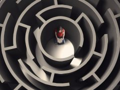 A woman reads a book while stuck in a large maze.